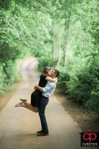 Couple kissing on a farm road.