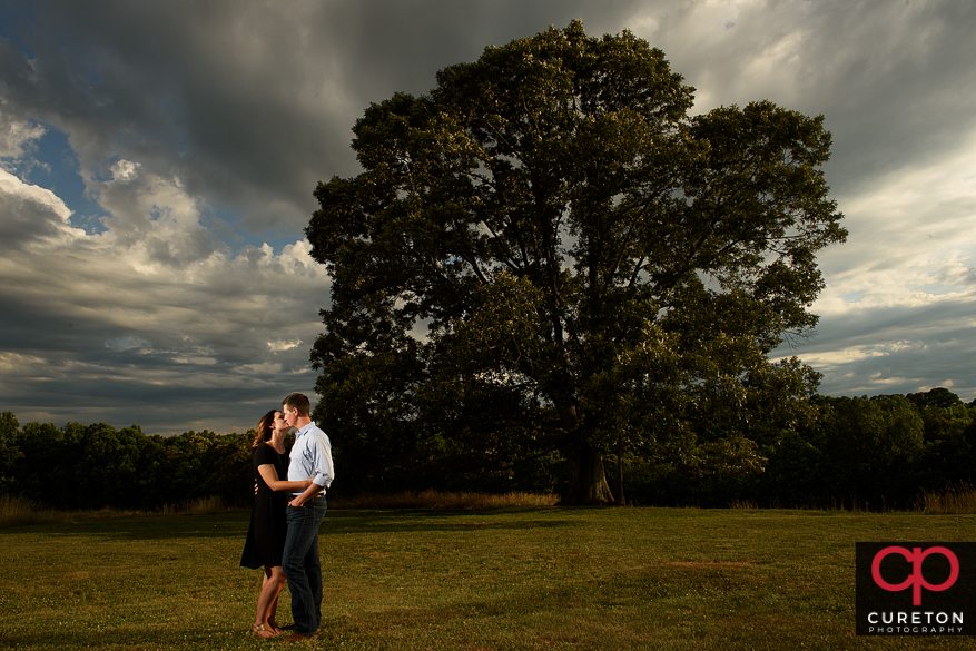Couple kissing at the tree at Greenbrier Farms in Easley,SC.