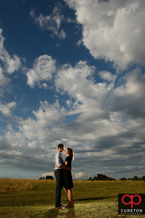Couple hugging with an epic sky background.