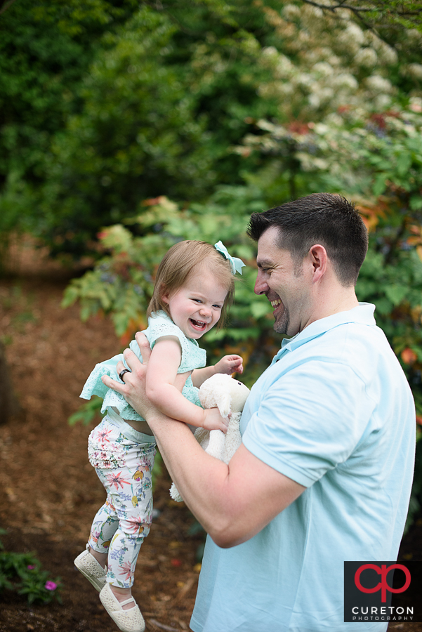 Dad and daughter playing during a family photo session at the Rock Quarry Garden in Greenville,SC.