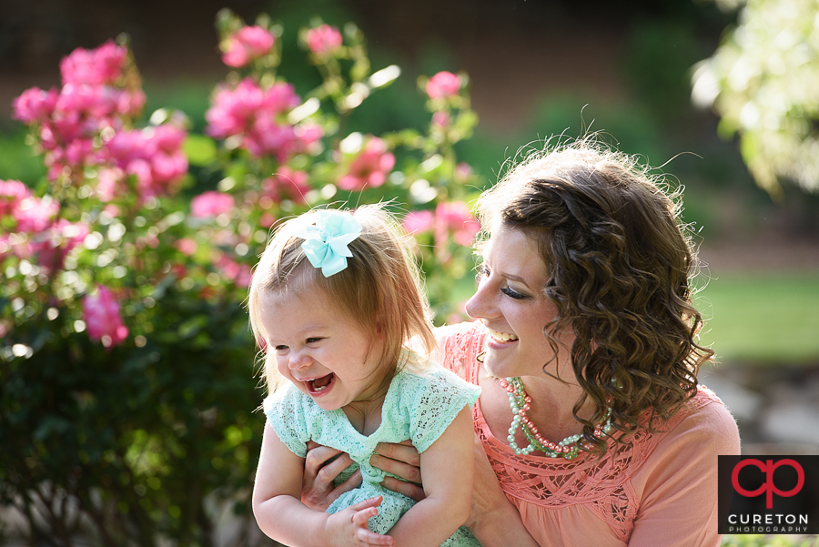 Mom and daughter laughing during a family session.