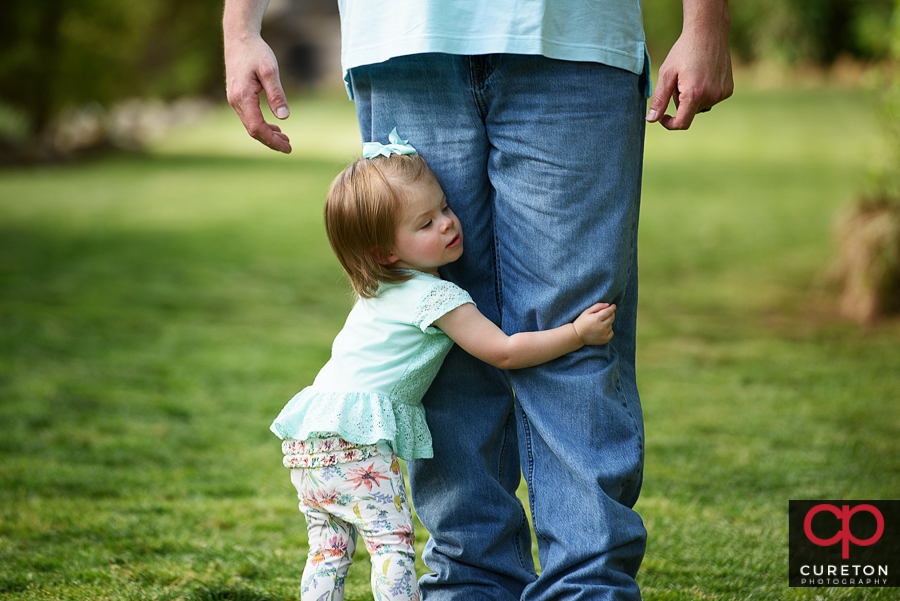 Toddler huggin daddy's legs during a photo session.