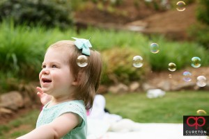 Toddler with bubbles in the park.