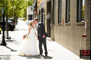 Bride kissing groom after a first look in downtown Greenville,SC.