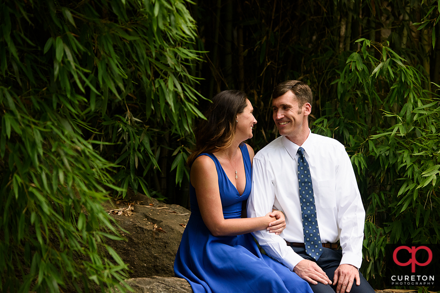 Engaged couple smiling at each other during a Greenville park engagement session.