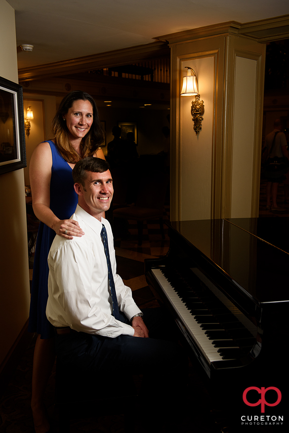 Engaged couple sitting at a piano at the Westin Poinsett in Greenville,SC.