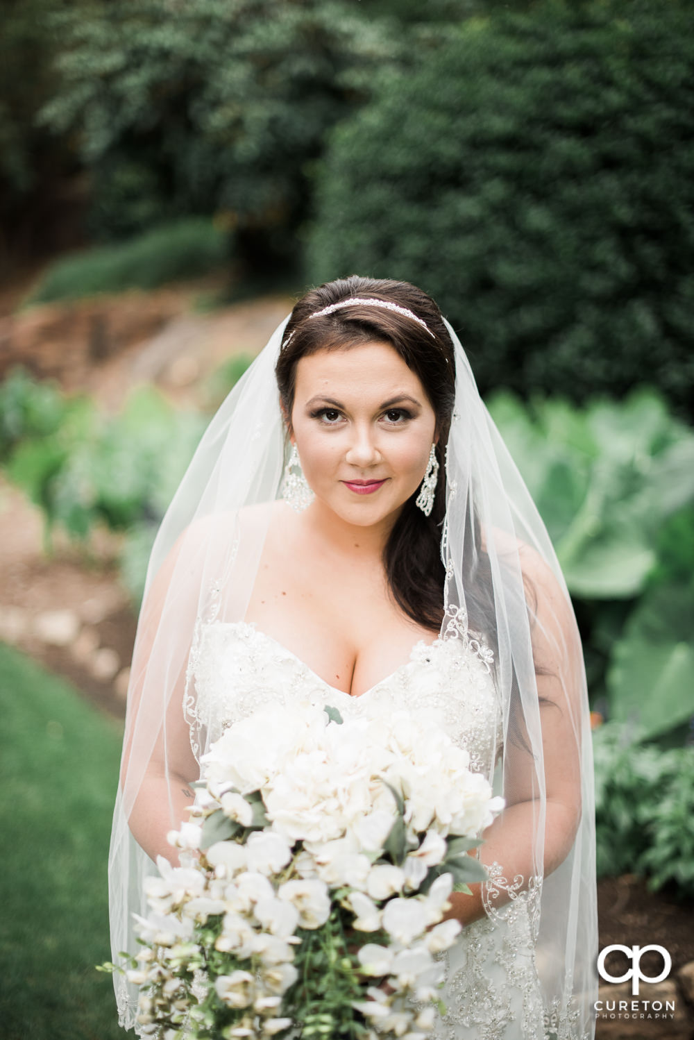 Bride with long veil wrapped around her during her bridal session at the Greenville Rock Quarry Garden.