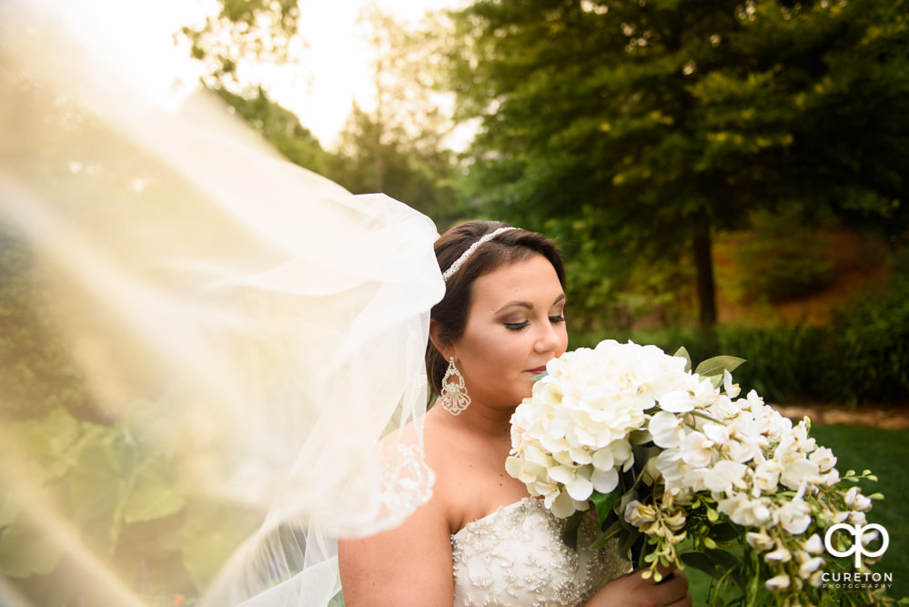 Bride with her veil blowing in the wind.