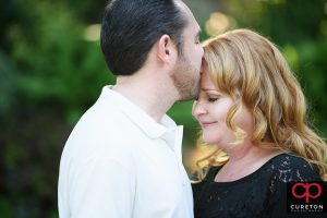 A man kissing his fiancee on the forehead during a falls park engagement session.