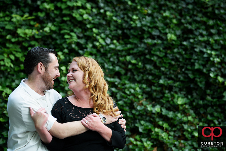 Beautiful shot of a future bride and groom in front of a wall of ivy.