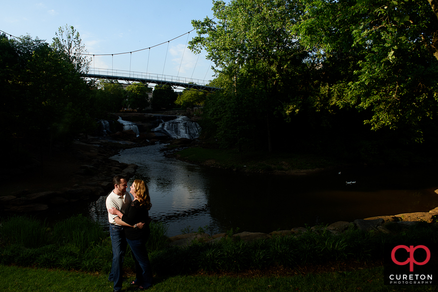 Engaged couple with liberty bridge in the background.