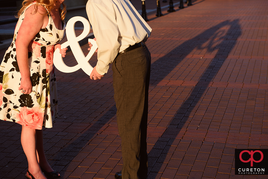 Engaged couple holding an ampersand.