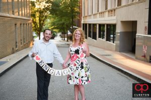 Engaged couple holding a sign.