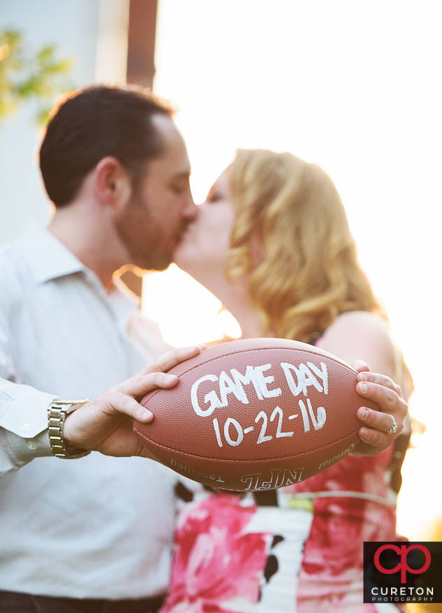 Engaged couple holding a football with the wedding date on it.