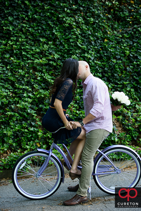 Engaged couple on a vintage bicycle.