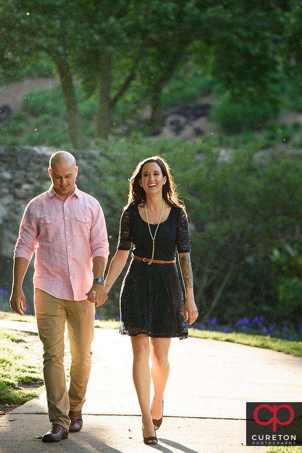 Engaged couple walking in a downtown park.