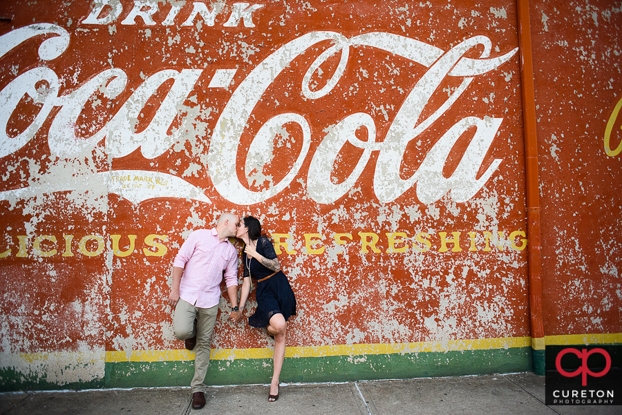 Engaged couple standing near a Coca Cola sign in downtown Greenville.