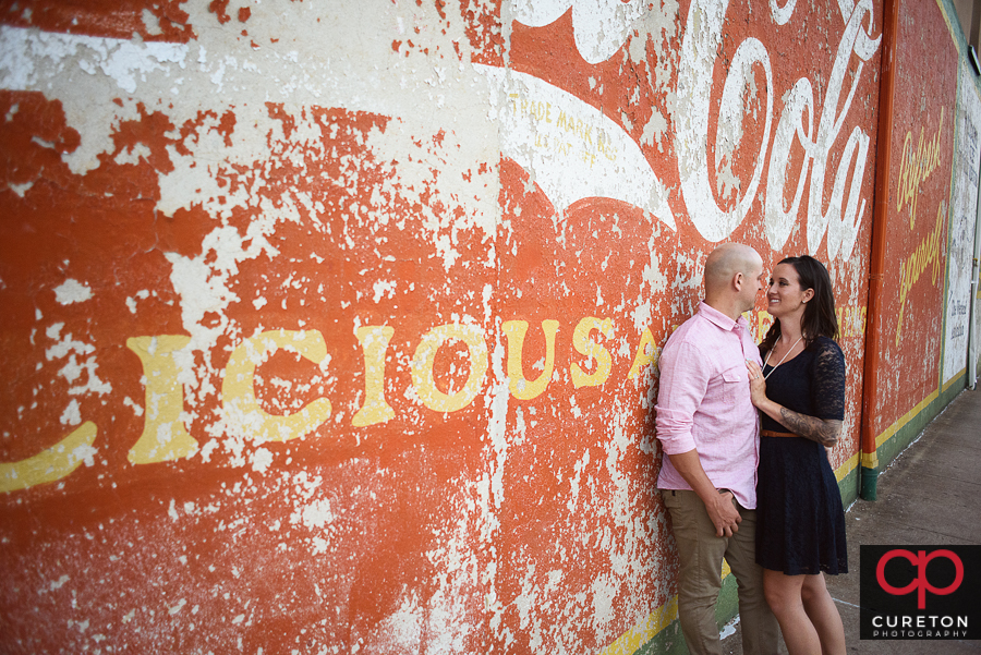 Engaged couple standing near a Coca Cola sign in downtown Greenville,SC.