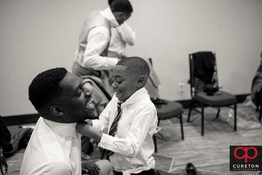 Ring bearer helping a groomsmen with his tie.