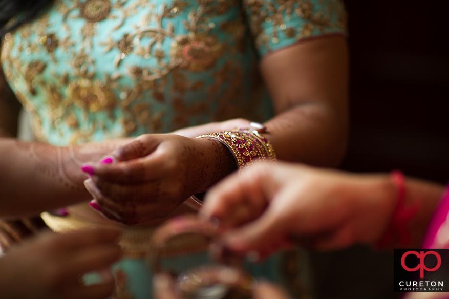 Indian bride putting on bracelets.