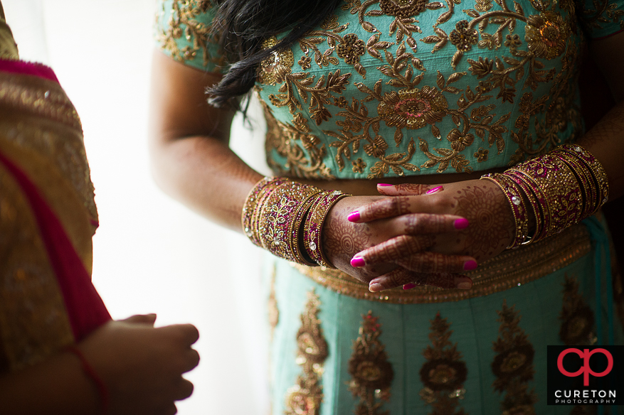 Indian bride putting her jewelry on.