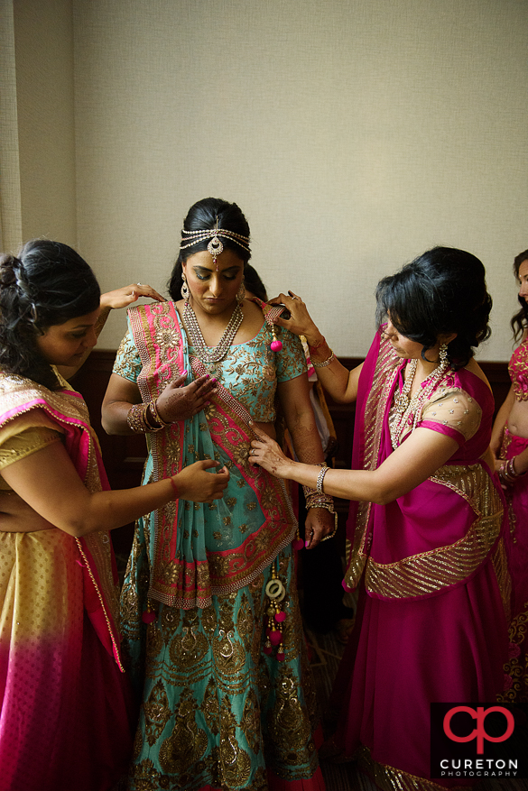 Bride and her sisters getting ready for her Indian wedding.