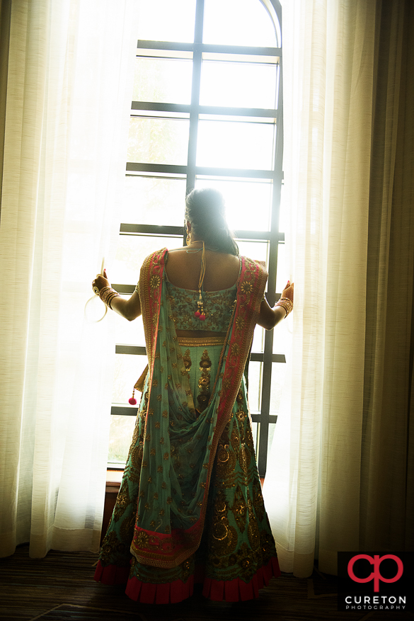 Beautiful Indian bride looking out of the sunlit window.