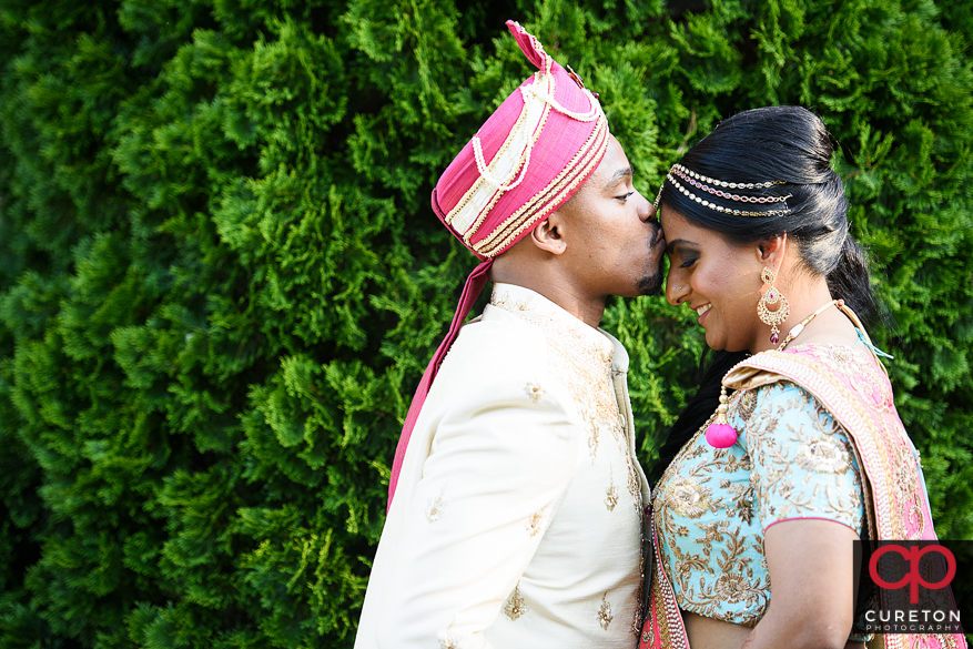 Groom kissing is bride on the forehead.