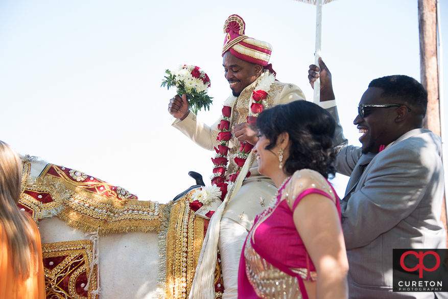 Groom making his entrance on a horse before the Indian wedding.