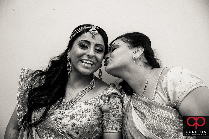 Bride's sister kisses her on the cheek.