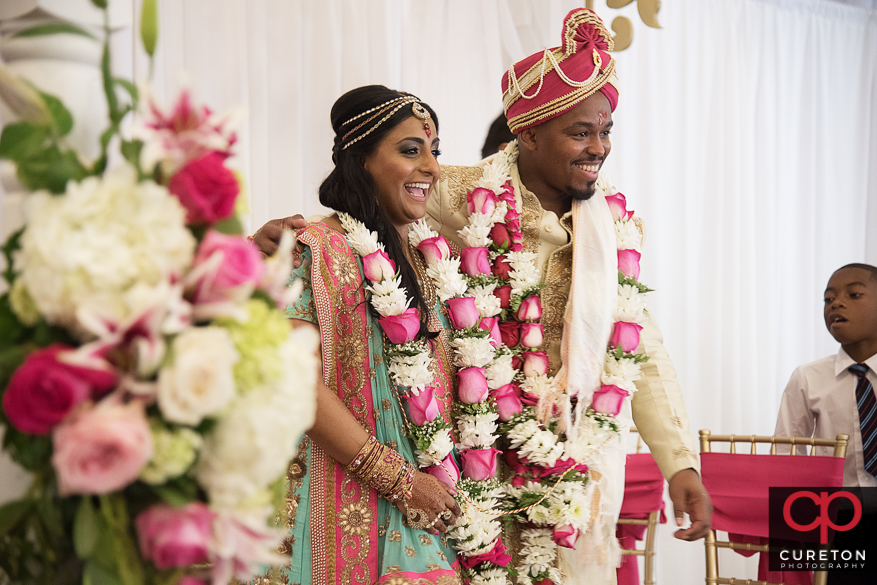 Indian bride and groom smiling during their wedding ceremony.