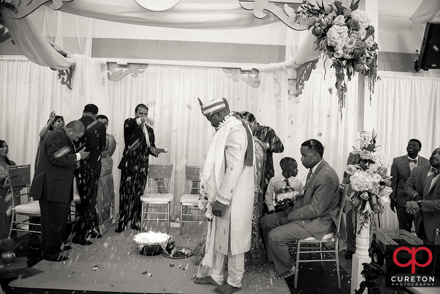The bride and groom get flowers thrown at them during their wedding ceremony.
