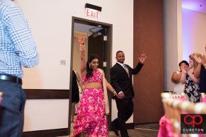 Indian bride and groom making an entrance into the wedding reception.