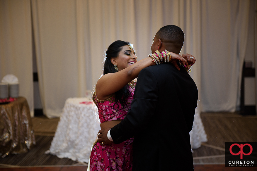 Indian bride and groom sharing a first dance at their reception.