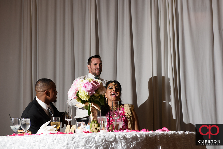 The bride and groom enjoy the toasts at their reception.