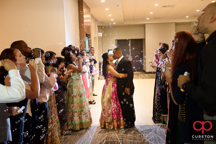 The bride and groom leaving their Indian wedding reception at Embassy Suites in Greenville,SC through a sea of bubbles.