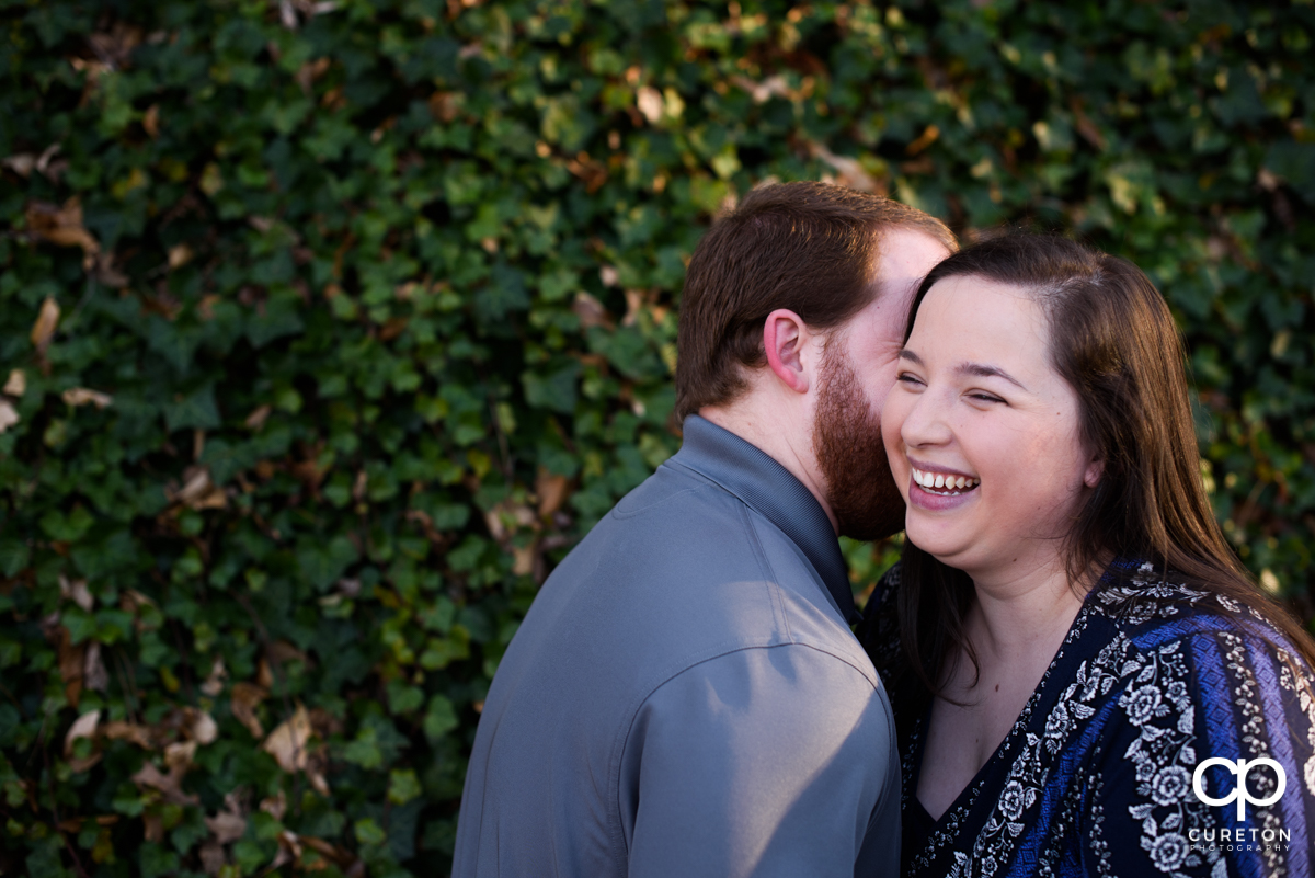 Man making his fiancee laugh during a Greenville,SC park engagement session.