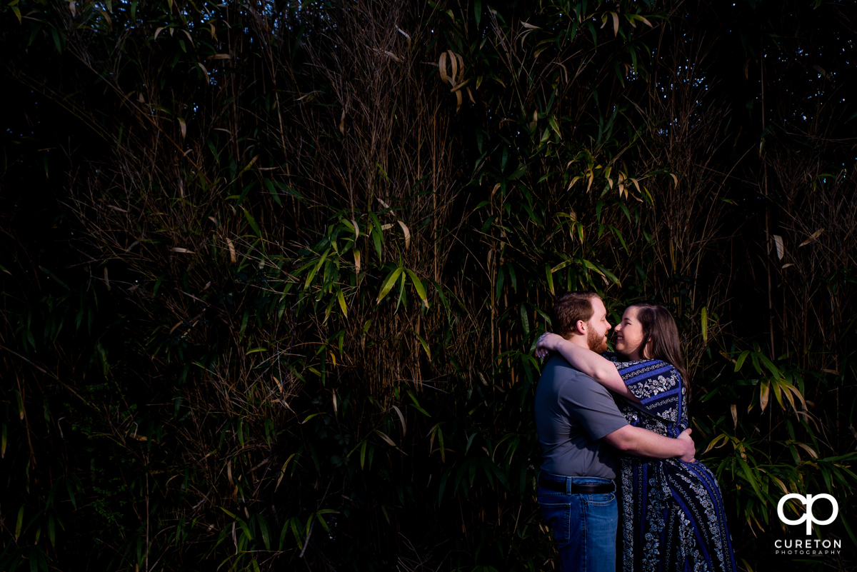 Man hugging his future wife during a Greenville,SC park engagement session.