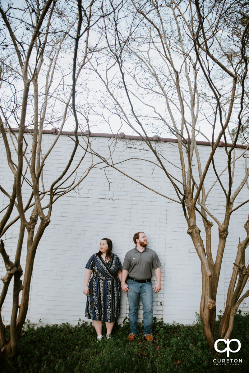 Engaged couple standing against a white brick wall on Main St. during a Greenville,SC park engagement session.