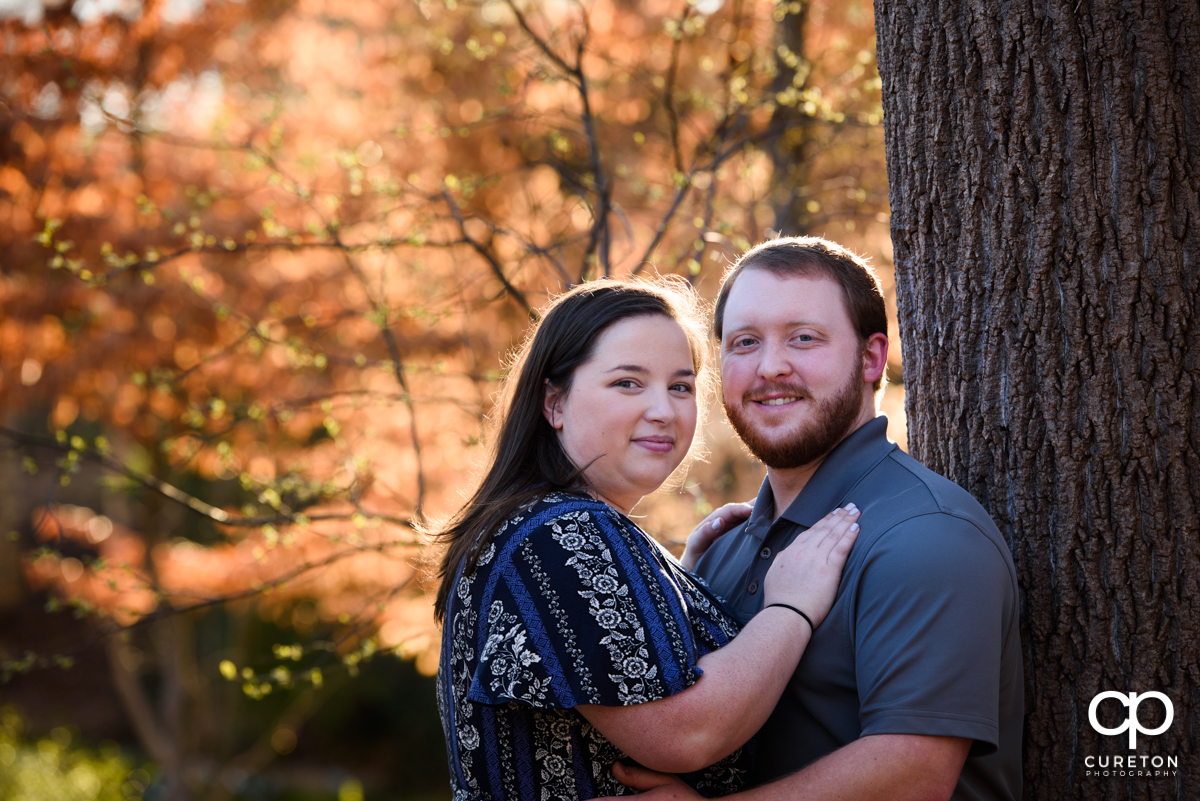 Engaged couple in the wooded area of a downtown park.