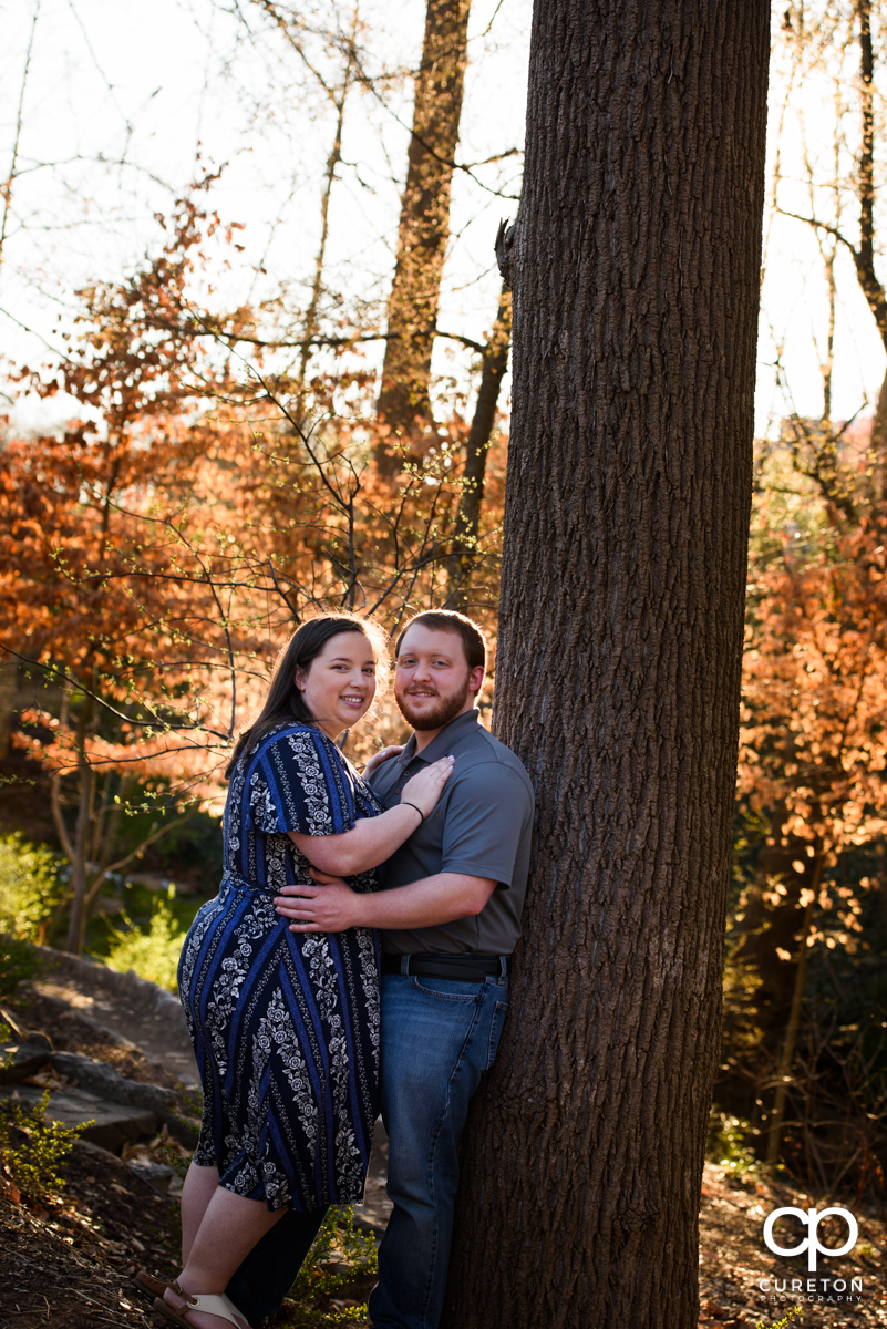 Engaged couple leaning against a tree.