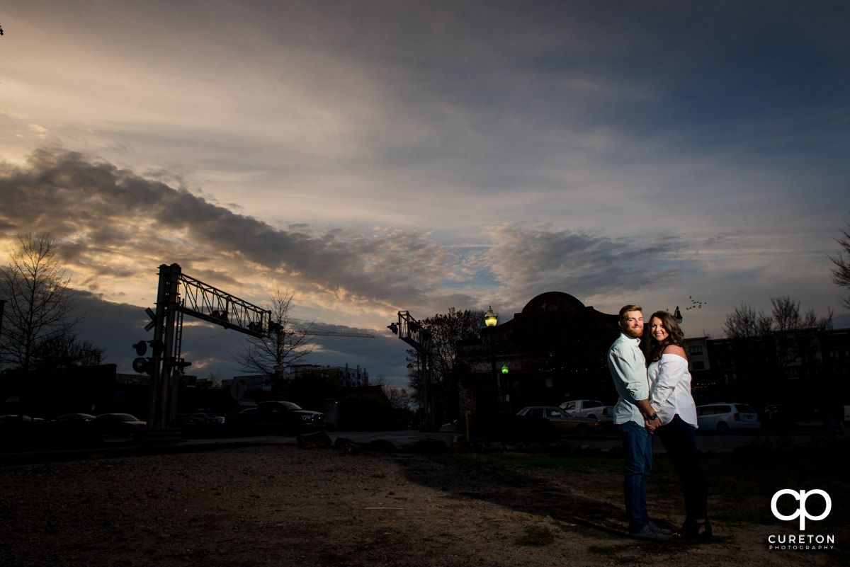 Husband and wife holding hands at sunset in front of Old Cigar Warehouse during an anniversary photo session in Greenville,SC.