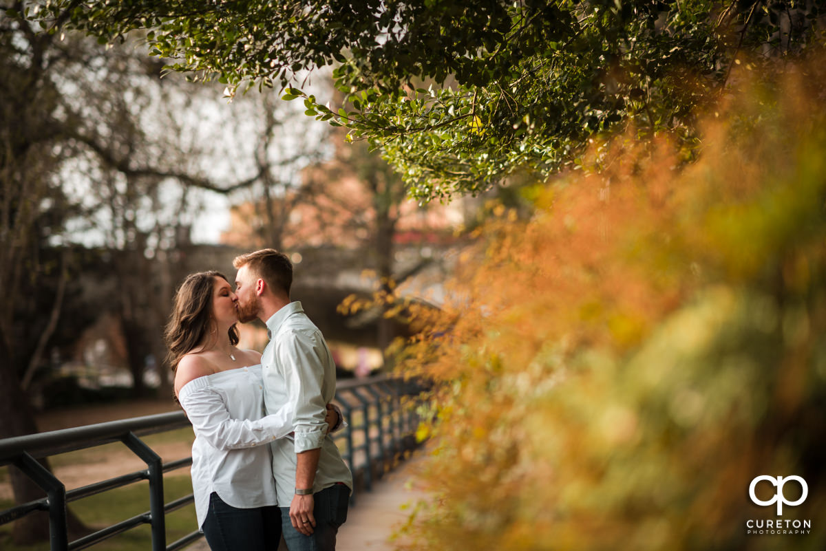 Man kissing his wife in the park during a Greenville,SC anniversary session.