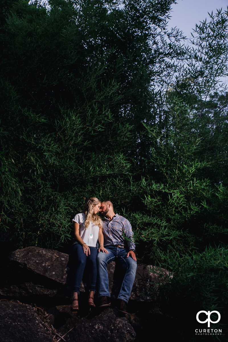 Future bride and groom sitting on a rock at The Rock Quarry Garden during an engagement session in Greenville,SC.