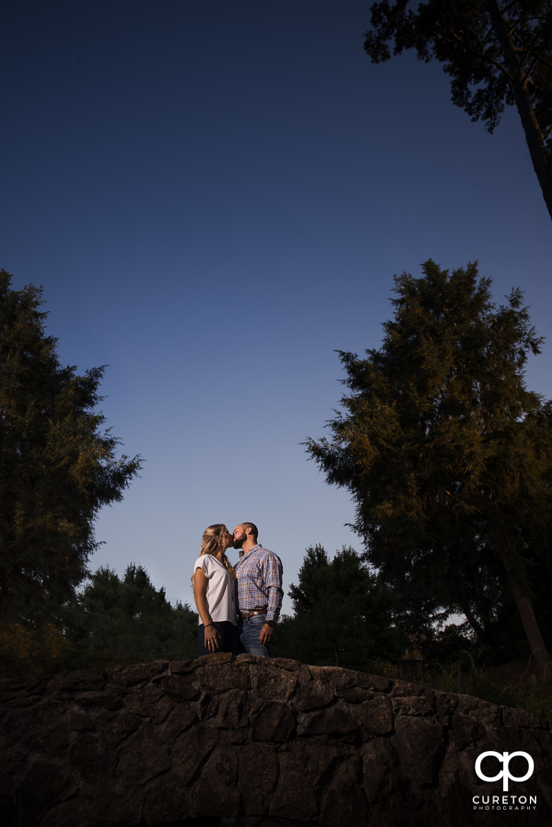 Bride and groom kissing on a bridge during their engagement session at The Rock Quarry Garden in Greenville,SC.