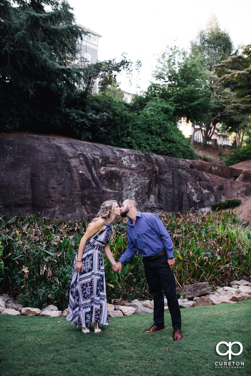 Engaged couple kissing in a downtown Greenville park at their engagement session.