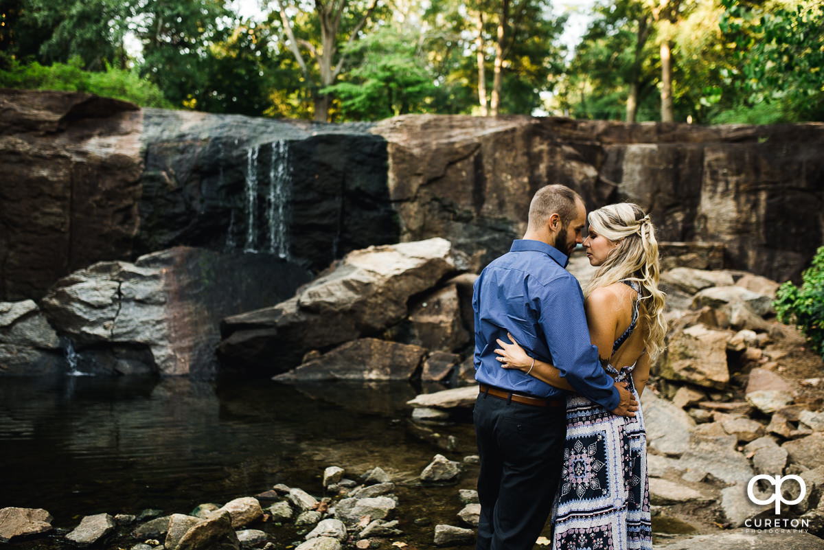 Engaged couple in front of a waterfall in Greenville at their engagement session.