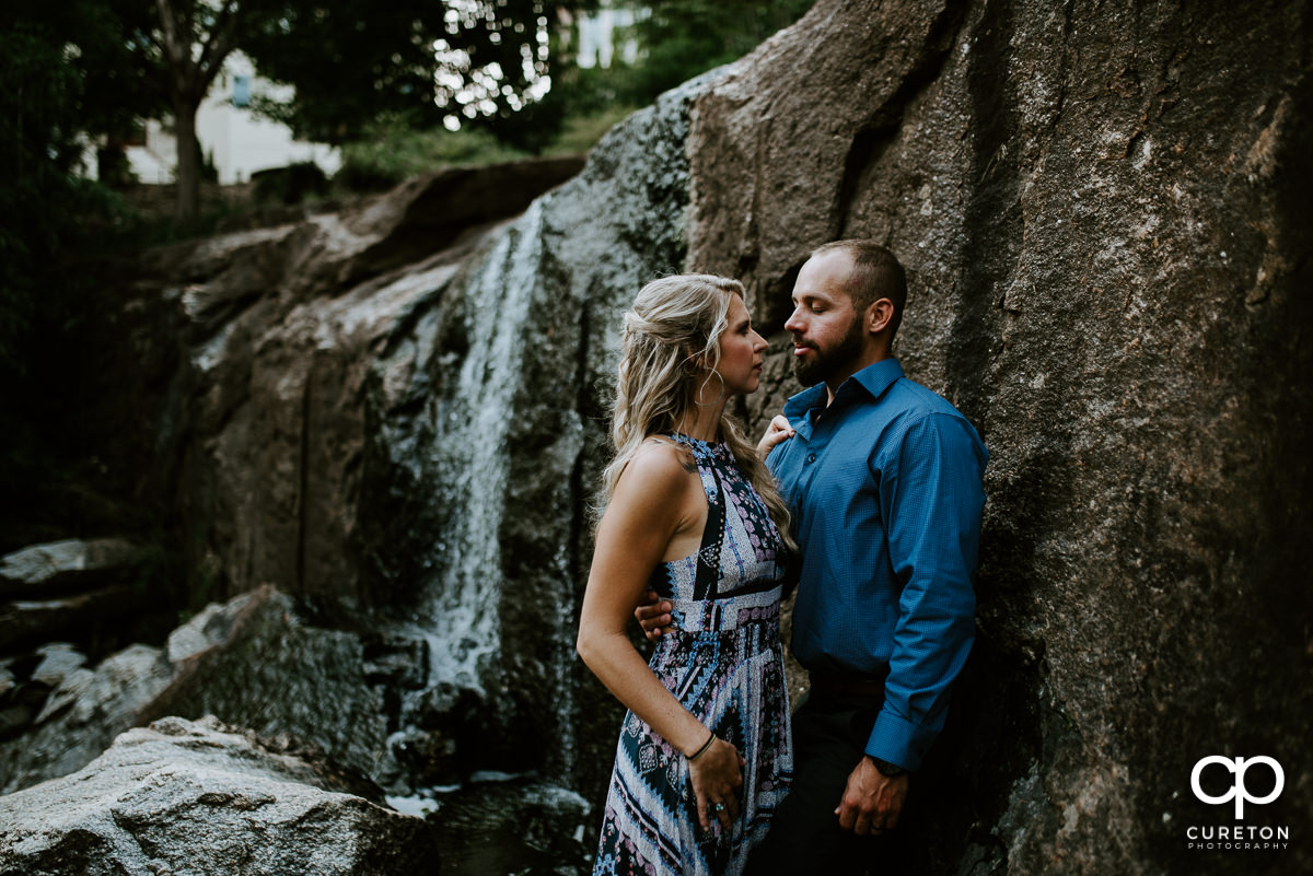 Engaged couple leaning on a rock in front of a waterfall in Greenville.