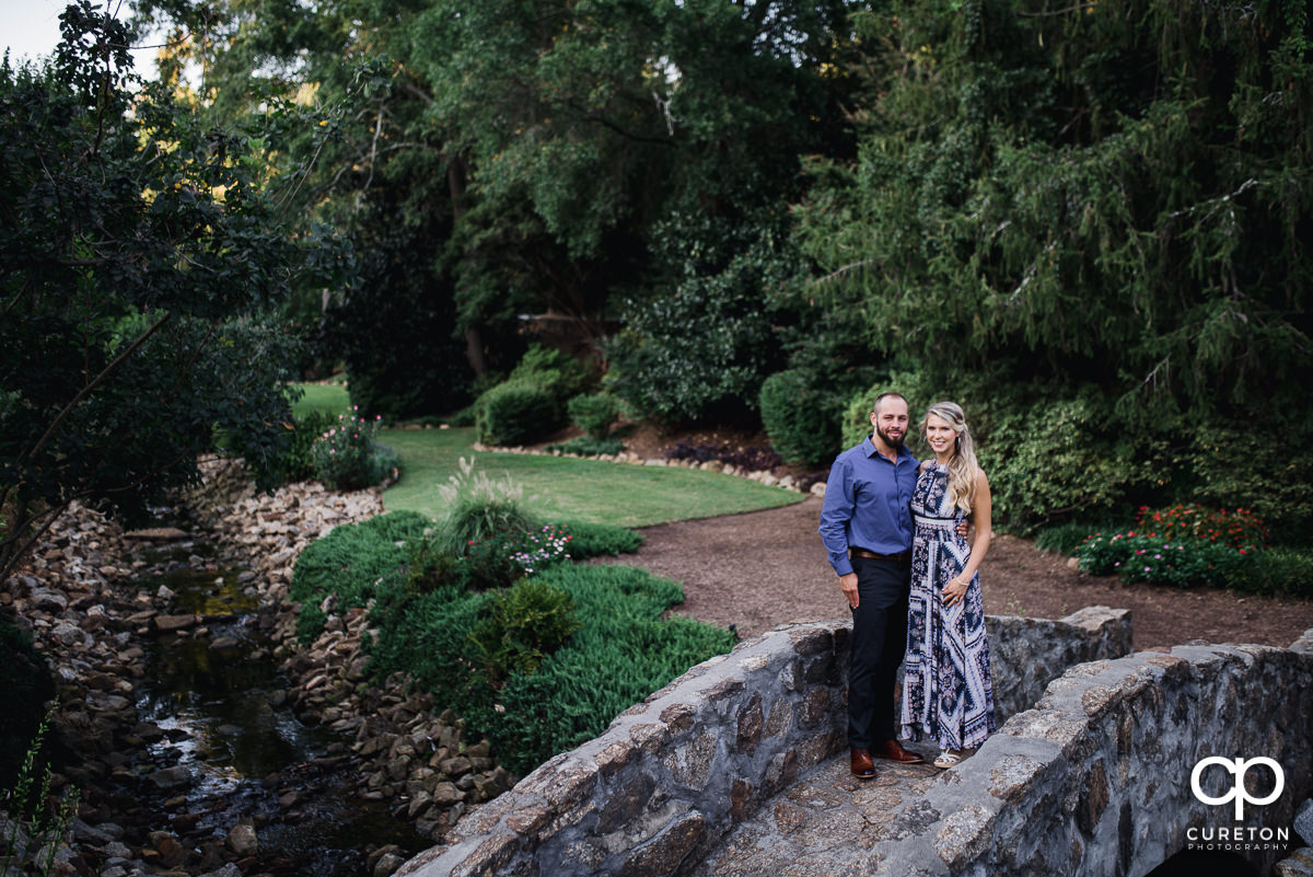 Engaged couple standing on the bridge at the Rock Quarry Garden in Greenville.