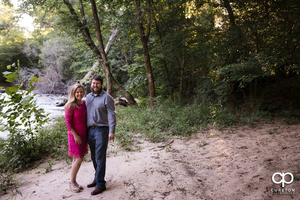 Engaged couple standing on the banks of the Enoree River during a summer engagement session in Greer,SC.